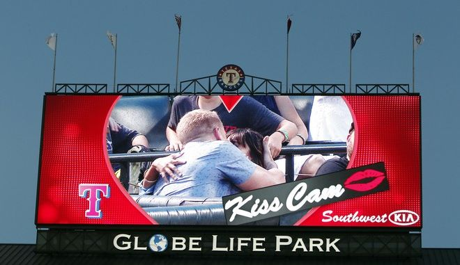 "Reality TV star ""The Bachelor"" Sean Lowe and wife Catherine Giudici are shown on the ""Kiss Cam"" during a baseball game between the Texas Rangers and Cleveland Indians, Friday, June 6, 2014, in Arlington, Texas. (AP Photo/Brandon Wade)"