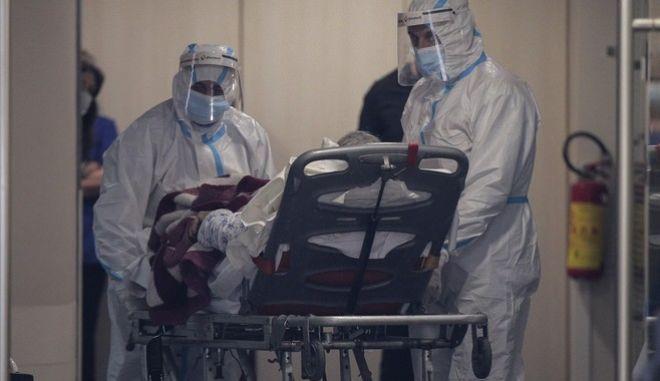 Ιατρικό προσωπικό μεταφέρει ασθενή με Covid-19