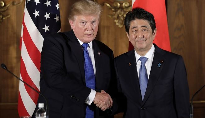 President Donald Trump, left,  shakes hands with Japanese Prime Minister Shinzo Abe during a joint news conference at the Akasaka Palace, Monday, Nov. 6, 2017, in Tokyo. Trump is on a five country trip through Asia traveling to Japan, South Korea, China, Vietnam and the Philippines.  (Kiyoshi Ota/Pool Photo via AP)
