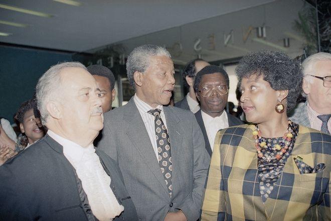 Ο Νέλσον Μαντέλα και η σύζυγός του αποχωρώντας από το Ανώτατο Δικαστήριο του Γιοχάνεσμπουργκ, 4 Φεβρουαρίου 1991, αφού η κ. Μαντέλα φάνηκε να αντιμετωπίζει κατηγορίες για απαγωγή και επίθεση. Στα αριστερά, ο Τζορτζ Μπίζος, ο οποίος υπερασπίστηκε τον Νέλσον Μαντέλα κατά τη διάρκεια της δίκης προδοσίας του στη δεκαετία του '60.