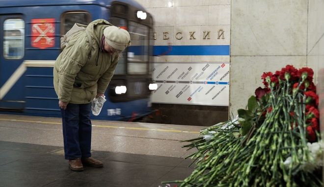 A woman pays her respects at a symbolic memorial at Tekhnologichesky Institute subway station in St. Petersburg, Russia, Tuesday, April 4, 2017. A bomb blast tore through a subway train deep under Russia's second-largest city St. Petersburg Monday, killing several people and wounding many more in a chaotic scene that left victims sprawled on a smoky platform.  (AP Photo/Dmitri Lovetsky)