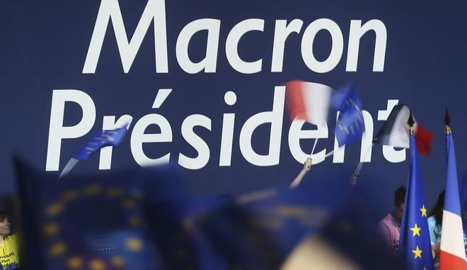 Supporters wave flags during independent centrist candidate Emmanuel Macron's meeting in Nantes, western France, Wednesday, April 19, 2017. Polls suggest Macron has a good chance of coming out on top of Sunday's first round and reaching the May 7 runoff. (AP Photo/David Vincent)