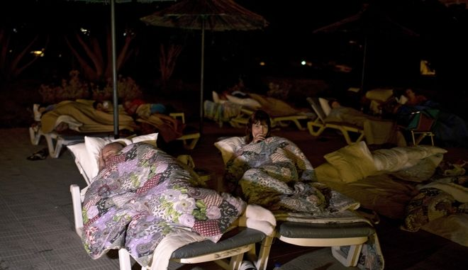 British tourists sleep on sun beds of a hotel following an earthquake in the Mediterranean island of Kos, Greece, late Friday, July 21, 2017. Causing panic but little serious damage, a powerful earthquake shook vacation resorts in Greece and Turkey, hurting nearly 500 people and killing two tourists who were crushed when a building collapsed on a popular bar in the Greek island of Kos. (AP Photo/Petros Giannakouris)