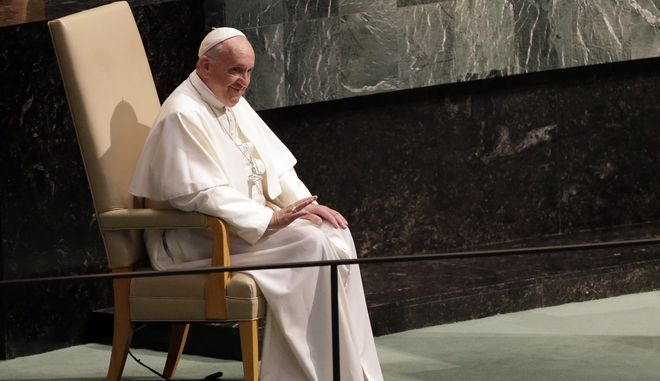 Pope Francis waves at the audience while sitting in the head of state chair before addressing the 70th session of the United Nations General Assembly, Friday, Sept. 25, 2015 at United Nations headquarters.  (AP Photo/Mary Altaffer)