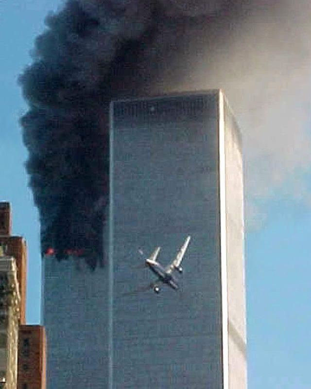 FILE - In this Sept. 11, 2001 file photo, United Airlines Flight 175 approaches the south tower of the World Trade Center in New York shortly before collision as smoke billows from the north tower. (AP Photo/Carmen Taylor)   Original Filename: Sept 11 Photo Package.JPEG-00491.jpg