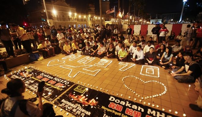 Malaysians gather during a candlelight vigil for passengers onboard the missing Malaysia Airlines Flight MH370, in Kuala Lumpur, Malaysia, Monday, April 7, 2014. An Australian ship detected two distinct, long-lasting sounds underwater that are consistent with the pings from aircraft black boxes in a major break in the month long hunt for the missing Malaysia Airlines jet, the search coordinator said Monday. (AP Photo/Vincent Thian)