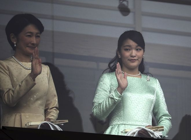 Japan's Princess Kiko, left, her daughters Princess Mako, center, and Princess Kako wave to well-wishers through the bullet-proof glass at a balcony of the Imperial Palace during New Year's public appearance with Emperor Akihito in Tokyo, Friday, Jan. 2, 2015. (AP Photo/Eugene Hoshiko)