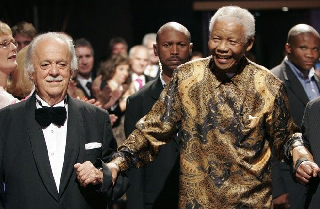 George Bizos, left, arrives for his 80th birthday party with former president Nelson Mandela, right, in Johannesburg Wednesday Nov. 12, 2008.  Few lawyers are considered to have done more to challenge the apartheid government than George Bizos, lifelong friend of Nelson Mandela. Bizos fled Greece in 1941 with his father, who had helped seven New Zealand soldiers escape German-occupied territory. Bizos helped shape South Africa's constitution and continues to be a passionate human rights activist. (AP Photo/Denis Farrell)