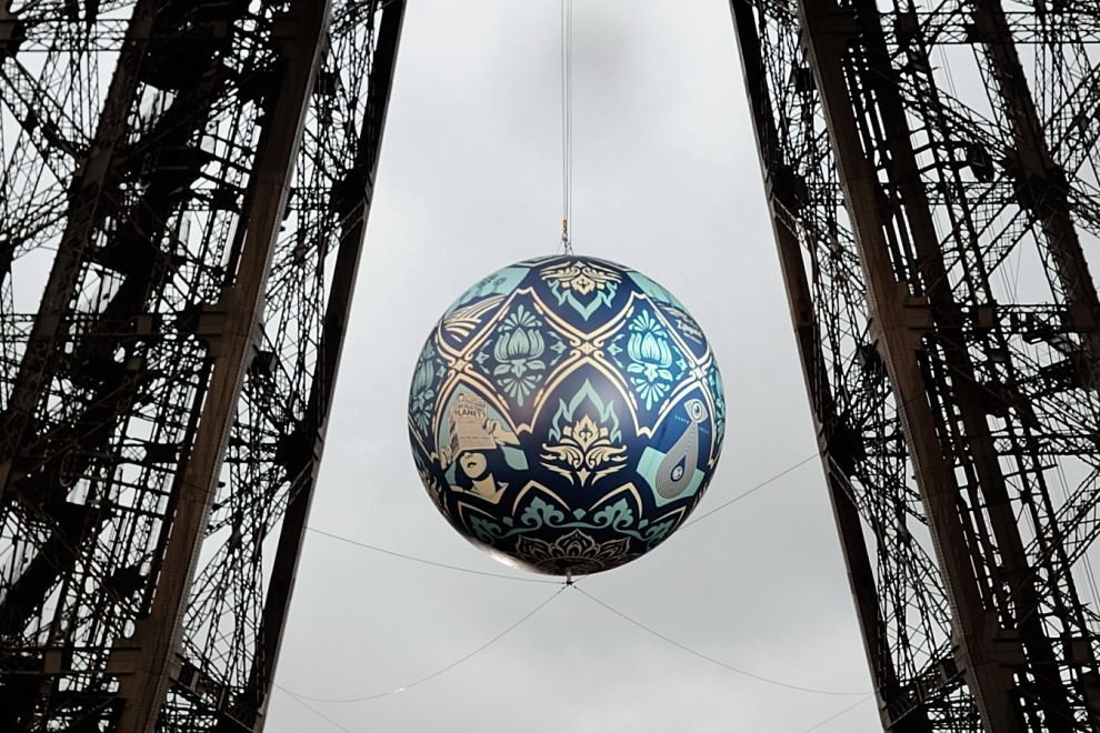 American street artist Shepard Fairey, aka Obey, 's latest piece 'Earth Crisis', a giant sphere themed on environment hangs between the first and second floor of the Eiffel Tower in Paris, Friday, Nov. 20, 2015. Obey's art piece which weighs 2,3 tons will be displayed until Nov. 26 as Paris will be hosting the climate change conference from Nov. 30-Dec. 11, 2015. (AP Photo/Binta Epelly)