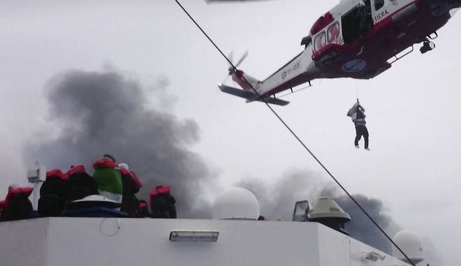 In this image taken from a Dec. 28, 2014 video and made available Wednesday, Dec. 31, 2014 a person is lifted from the deck of the Italian-flagged ferry Norman Atlantic by a rescue helicopter after it caught fire in the Adriatic Sea. More than 400 people were rescued from the ferry, most in daring, nighttime helicopter sorties that persisted despite high winds and seas, after a fire broke out before dawn Sunday on a car deck. Both Italian and Greek authorities have announced criminal investigations into the cause of the blaze. Italian authorities warned Tuesday that more bodies will likely be found when the blackened hulk of a Greek ferry is towed to Italy, as part of a criminal investigation into the fire that engulfed the ship at sea, killing at least 11 of the more than 400 people on bo