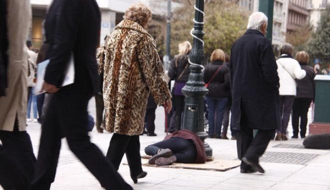 Επαίτης ζητά ελεημοσύνη από τους περαστικούς ξαπλωμένος στο πλακόστρωτο της πλατείας Συντάγματος κρατώντας στα χέρια του μια αγιογραφία του Αγ. Στυλιανού την Πέμπτη 12 Δεκεμβρίου 2013 (EUROKINISSI'ΓΙΩΡΓΟΣ ΚΟΝΤΑΡΙΝΗΣ)