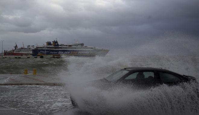 Αυτοκίνητο περνά μέσα από το νερό που έχει ξεβράσει η θάλασσα στο λιμάνη της Ραφήνας, πριν ακόμη φτάσει στην Αττική ο Κυκλώνας Ζορμπάς.