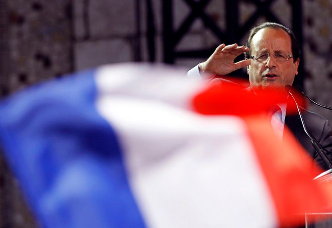 """FILE - In this Wednesday, March 28, 2012 file picture, a French flag flutters in the foreground as French Socialist Party candidate for the 2012 presidential elections Francois Hollande, delivers his speech as he campaigns in Nice, southern France. French President Francois Hollande announced Thursday that he would not seek a second term in next year's presidential election, saying he hoped to give his Socialist party a chance to win """"against conservatism and extremism"""" by stepping aside. (AP Photo/Christophe Ena, File)"""