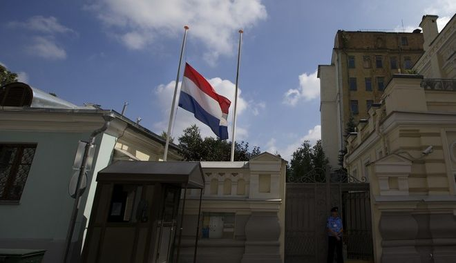 The Dutch flag flies at half-staff over the Dutch embassy in Moscow, Russia, Friday, July 18, 2014. Rescue workers, policemen and even off-duty coal miners were combing a sprawling area in eastern Ukraine near the Russian border where the Malaysian plane ended up in burning pieces Thursday, killing all 298 aboard. (AP Photo/Ivan Sekretarev)