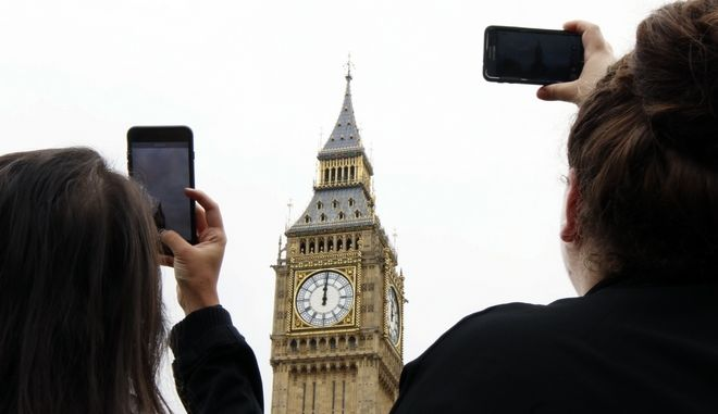 People record the last bell bong at Elizabeth Tower in London, Monday, Aug. 21, 2017. At noon, Big Ben's famous bongs sounded for the last time before major conservation works are carried out. The Elizabeth Tower, home to the Great Clock and Big Ben, is currently undergoing a complex programme of renovation work that will safeguard it for future generations. While this vital work takes place, the Great Bell's world famous striking will be paused until 2021 to ensure the safety of those working in the Tower.(AP Photo/Leonore Schick)