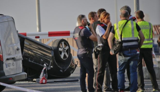 Police officers speak near an overturned car at the spot where terrorists were intercepted by police in Cambrils, Spain, Friday, Aug. 18, 2017. The police force for Spain's Catalonia region says the five suspects shot and killed in the resort town of Cambrils were carrying bomb belts, which have been detonated by the force's bomb squad. (AP Photo/Emilio Morenatti)