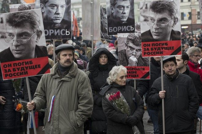 People carry portraits of opposition leader Boris Nemtsov, who was gunned down on Friday, Feb. 27, 2015 near the Kremlin, with words reading ' he died for the future of Russia!' in Moscow, Russia, Sunday, March 1, 2015. Russian investigators, politicians and political commentators on state television on Saturday covered much ground in looking for the reason Nemtsov was gunned down in the heart of Moscow, but they sidestepped one possibility, that he was murdered for his relentless opposition to Putin. (AP Photo/Pavel Golovkin)