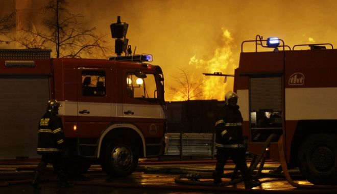 Firefighters walk past fire that burst inside of the Incheba Expo exhibition ground in Prague, Czech Republic, Thursday, Oct. 16, 2008. (AP Photo/Petr David Josek)