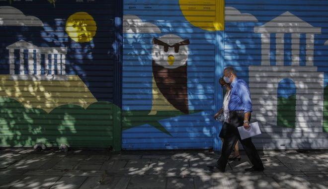 Άνθρωποι με μάσκες για τον κορονοϊό περπατούν στην Αθήνα