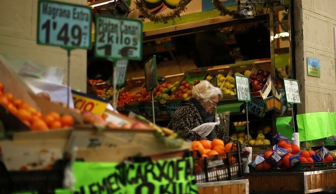In this photo taken Sunday, Dec. 17, 2017, a woman buys items at a fruit store in Barcelona, Spain. Jittery businessmen in Catalonia have put their investment plans on ice as they brace for the region's parliamentary election on Thursday, Dec. 21, 2017. Investors are spooked by signs the recent tumult over its latest bid to secede from Spain is hurting the local economy. Recent figures show Catalan retail sales and tourist arrivals are falling while unemployment edges higher. (AP Photo/Manu Fernandez)