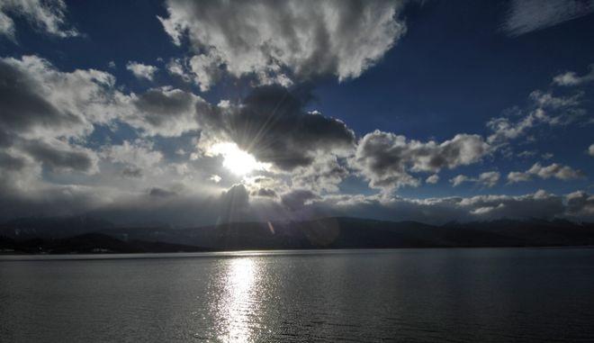 Σύννεφα πάνω από την λίμνη Πλαστήρα με φόντο τις κορυφές των Αγράφων πάνω από το χωριό Νεοχώρι.