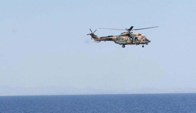 A Turkish military Cougar helicopter searches for survivors of sea accident as crew members of the Turkish frigate, TCG Gemlik, rushes to the aid of some of them during a mock search and rescue exercise by Turkish and Turkish Cypriot forces on Wednesday, June 17, 2009 off Cyprus, where tensions run high over Greek Cypriot plans to expand search for oil and gas despite strong objections by Turkey.  (AP Photo/ Selcan Hacaoglu)