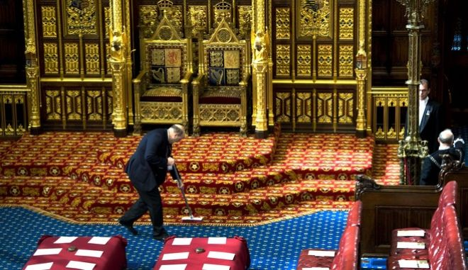An attendant does a final clean up in the chamber of the House of Lord's, Palace of Westminster, London Tuesday May 25, 2010 prior to the Queen opening the British parliament. Queen Elizabeth II has opened Parliament nearly 60 times, but she will have an unfamiliar task Tuesday as she sets out the legislative program of a coalition government _ the country's first since World War II. (AP Photo/Arthur Edwards, Pool)