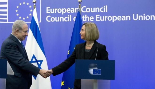 European Union High Representative Federica Mogherini, right, shakes hands with Israeli Prime Minister Benjamin Netanyahu after participating in a media conference at the EU Council building in Brussels on Monday, Dec. 11, 2017. (AP Photo/Virginia Mayo)