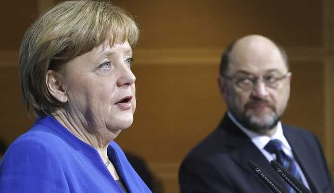 German Chancellor Angela Merkel, left, speaks during a joint statement with Social Democratic Party Chairman Martin Schulz after the exploratory talks between Merkel's Christian Democratic block and the Social Democrats on forming a new German government in Berlin, Germany, Friday, Jan. 12, 2018. (AP Photo/Michael Sohn)