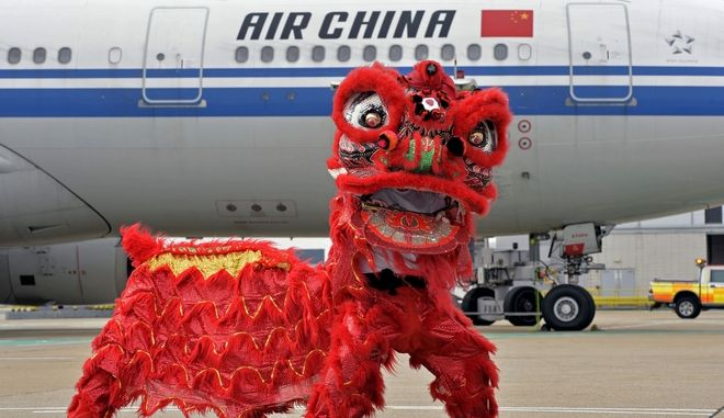 People inside a Chinese Lion costume pose,  at London Gatwick Airport, to celebrate the planned return of Air China's scheduled flights to Beijing, Sunday, March 30, 2014. Air China restarted flights from Gatwick to Beijing on Sunday, after cancelling the route last winter.  (AP Photo)