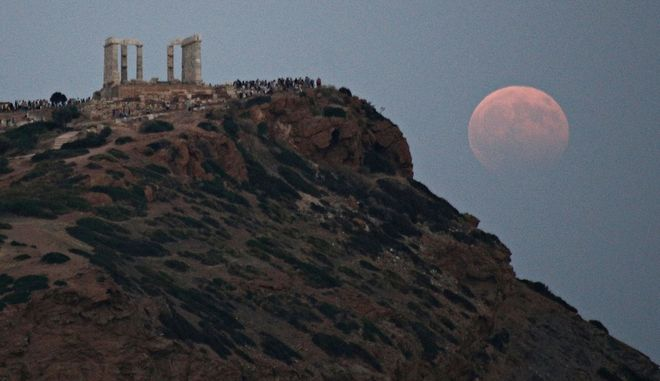 The full moon rises over the ancient temple of Poseidon on cape Sounio in southern Attica, Greece on Aug. 7, 2017/      7 , 2017