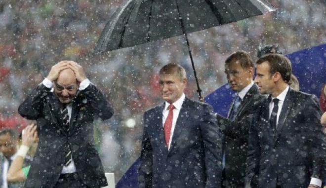 Βλαντιμίρ Πούτιν και Εμανουέλ Μακρόν μαζί υπό βροχήν, μετά τη λήξη του τελικού στο Μουντιάλ της Ρωσίας, στις 15 Ιουλιου 2018