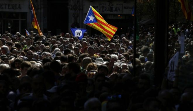 A crowd of pro-independence protestors gather outside the headquarters of the region's department of economic affairs in Barcelona, Spain, Wednesday, Sept. 20, 2017.  Spanish police arrested at least 12 people Wednesday in raids on Catalan government offices, news reports said, as national authorities intensified a crackdown on the region's preparations for a secession vote that Spain says is illegal. (AP Photo/Manu Fernandez)