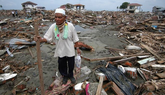 An Acehnese man walks through debris left behind by a massive tsunami in the town of Banda Aceh, on the Indonesian island of Sumatra in this January 1, 2005 file photo. Frustrated, living in tents and jobless, survivors of last December's tsunami that killed up to 232,000 people around the Indian Ocean are struggling to rebuild six months after one of history's worst natural calamities. In the countries most affected -- Indonesia, Sri Lanka, India and Thailand -- survivors gripe that reconstruction of homes, the rebuilding of schools and the creation of work has barely begun as overwhelmed local governments to cope. Photo taken on January 1, 2005.  REUTERS/Yusuf Ahmad/File