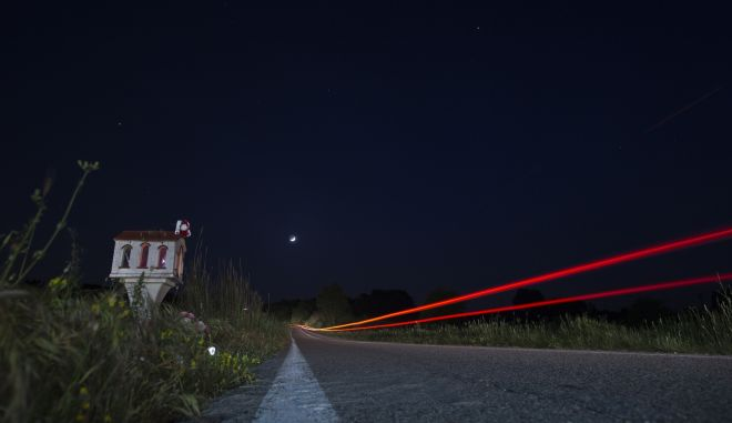 In this photo taken with a slow shutter speed on Friday, April 28, 2017, a car passes a roadside shrine near the village of Efyra, in the Peloponnese region of southern Greece. The shrine marks the spot where at dusk on Oct. 18, 2009, 19-year-old Nikos Staikopoulos lost control of his speeding car, crashed and died. Tens of thousands of such shrines punctuate Greeces roadside scenery, a common sight in a country that has one of the European Unions worst road fatality rates. (AP Photo/Petros Giannakouris)