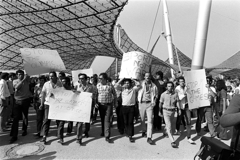 Διαδηλωτές έξω από το Ολυμπιακό Χωριό του Μονάχου, ζητούν να διακοπούν οι αγώνες ενώ εξελίσσεται η ομηρία των Ισραηλινών (5/9/1972).