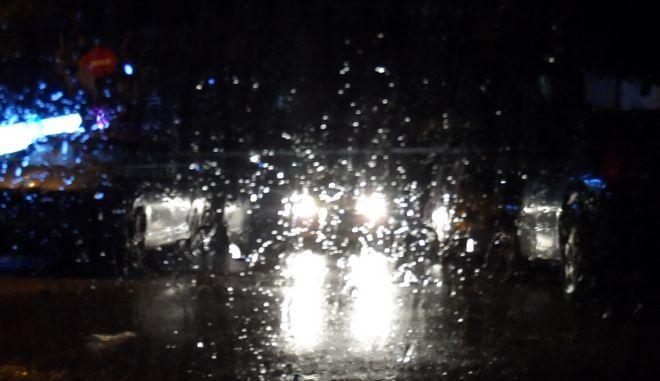 Τα φώτα ενός αυτοκινήτου διακρίνονται πίσω από το βρεγμένο παρμπρίζ ενός άλλου