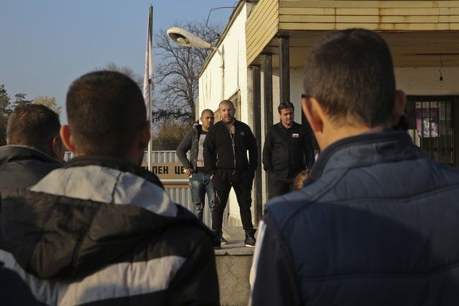 A local man  Dinko Valev, center, addresses locals gathered in protest at the fence of the Harmanli registration center as Bulgarian army soldiers are deployed in Harmanli, Bulgaria on Friday, Nov. 25, 2016. Some 400 migrants have been detained after clashes with police at a refugee camp in southern Bulgaria, that left several injured. Another 15 migrants have been arrested for damaging property, police said on Friday.(AP Photo/Visar Kryeziu)