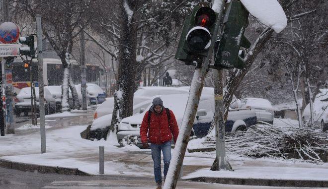 Άντρας περπατά στον δρόμο ενώ χιονίζει.