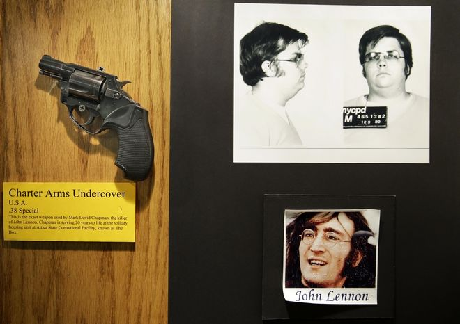 The gun used by Mark David Chapman to kill John Lennon is displayed next to their pictures at a small museum in the Forensic Investigation Division of the New York Police Department in New York, Tuesday, Dec. 8, 2015. Today is the anniversary of Lennon's death; he was killed 35 years ago by Chapman in New York.  (AP Photo/Seth Wenig)