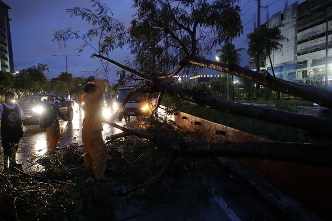 Government workers cut a toppled tree due to strong winds from Typhoon Goni in Manila, Philippines, Sunday, Nov. 1, 2020. The super typhoon slammed into the eastern Philippines with ferocious winds early Sunday and about a million people have been evacuated in its projected path, including in the capital where the main international airport was ordered closed. (AP Photo/Aaron Favila)