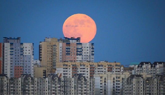 A full moon rises above apartments in Minsk, Belarus, Thursday, May 7, 2020. (AP Photo/Sergei Grits)