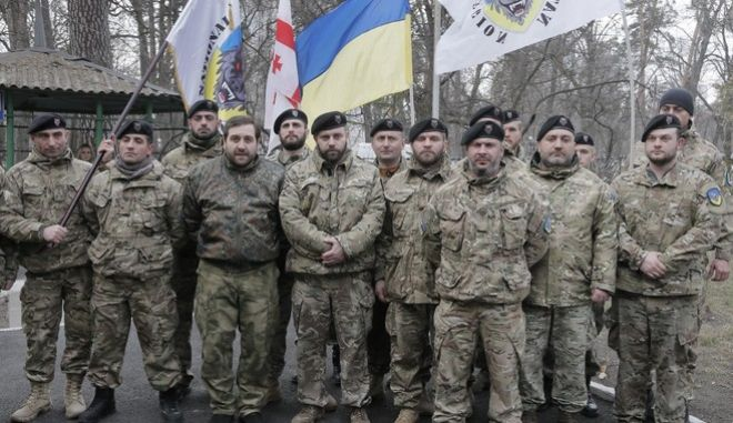 Officers of the Georgian National Legion volunteer battalion pose for a photo prior to their departure to the area of the war conflict in Ukraine's east, in Kiev, Ukraine, Tuesday, March 15, 2016. The Georgian National Legion consists mostly of Georgians, but there are also the US, French and Belgian citizens. (AP Photo/Efrem Lukatsky)