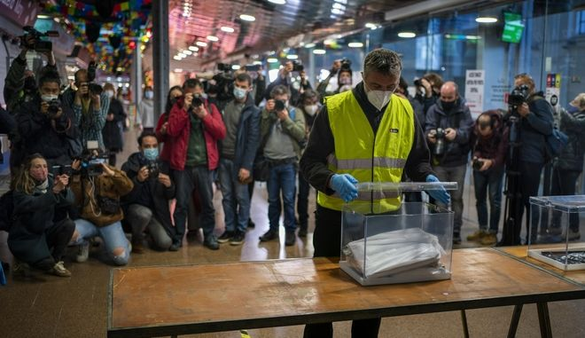 Members of the media take photographs as a city hall employee sets up a polling station at a market as part of a rehearsal for the media for the upcoming regional election in Barcelona, Spain, Wednesday, Feb. 10, 2021. Catalan regional elections will be held on Sunday. (AP Photo/Emilio Morenatti)