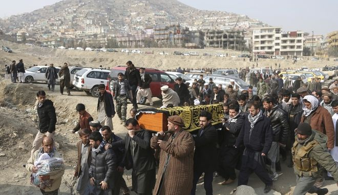 Men carry the coffin of a relative who died in Saturday's deadly suicide attack in Kabul, Afghanistan, Sunday, Jan. 28, 2018. The deadly explosion caused by a suicide bomber driving an ambulance in the capital. (AP Photo/Rahmat Gul)