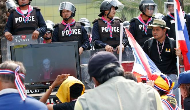 epa03957858 Thai anti-government protesters listen as the Constitution Court judge seen on a television screen (L), reads the verdict at the Constitutional Court in Bangkok, Thailand, 20 November 2013. Thailand's Constitutional Court on 20 November 2013, ruled that a recent amendment of the charter that changed the selection process for senators was unconstitutional, aborting it. The judges voted five to four that the amendment of article 111 covering the selection process of the Senate was a breach of the 2007 constitution as it undermined checks and balances in the political system. While thousands of protesters from the opposition and anti-government groups and the government support groups gather for the Constitution Court's verdict in downtown Bangkok.  EPA/NARONG SANGNAK
