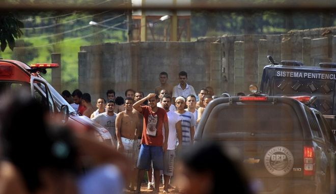 Prisoners, back, try to contact relatives after a rebellion at the Colonia Agroindustrial prison in the Aparecida de Goiania Complex, in the state of Goias, Brazil, Monday, Jan. 1, 2018. Inmates from rival gangs battled at the prison Monday, leaving several dead and more than a dozen injured, authorities told the Brazilian news site G1. (Claudio Reis/O Popular via AP)