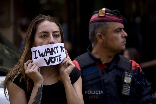 A demonstrator protests covering her mouth with a banner next to a Catalan police officer in Barcelona, Spain, Wednesday, Sept. 20, 2017. Catalan pro-independence supporters have scuffled with Spanish Civil Guard officers as they left a building, escorting a government official arrested as part of a crackdown by national authorities on Catalonia's plans to hold a secession referendum. (AP Photo/Emilio Morenatti)