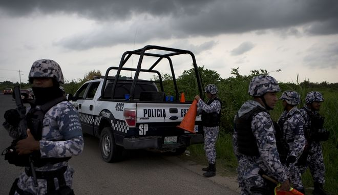 In this July 1, 2017 photo, Veracruz state police dismantle a temporary road block in Coatzacoalcos, Mexico. Veracruz is among the newly contested battlegrounds as Mexico is seeing its highest murder rate in 20 years, outpacing the worst days of the drug war in 2011. The violence is fueled by drug cartels splintering and battling each other for control as old alliances dissolve and new gangs arise.(AP Photo/Rebecca Blackwell)