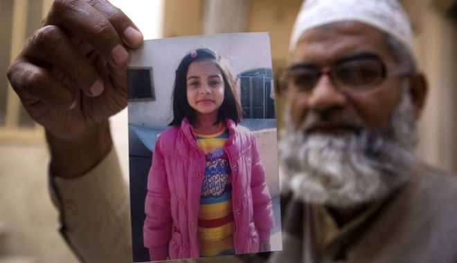 In this Thursday, Jan. 18, 2018 photo, Mohammed Amin shows a picture of his seven year-old daughter, Zainab Ansari in Kasur, Pakistan. The brutal rape of Zainab, whose body was left in a garbage dump earlier this month, has roiled Conservative Pakistan and revealed a sexual predator who has raped and killed at least 11 girls in Zainab's hometown of Kasur. He is still at large. (AP Photo/B.K. Bangash)